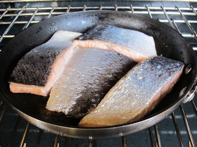 Searing salmon fillets in a skillet.