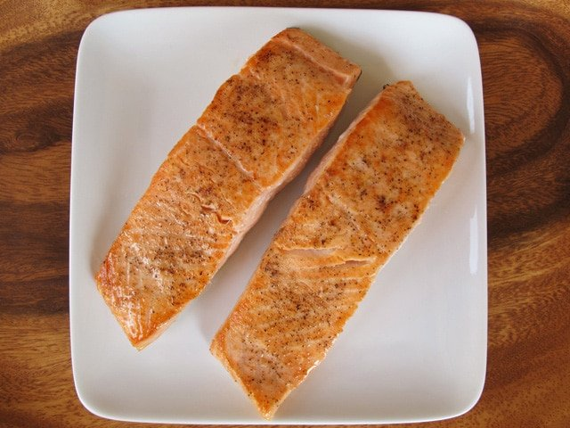 Seared salmon fillets on a plate.