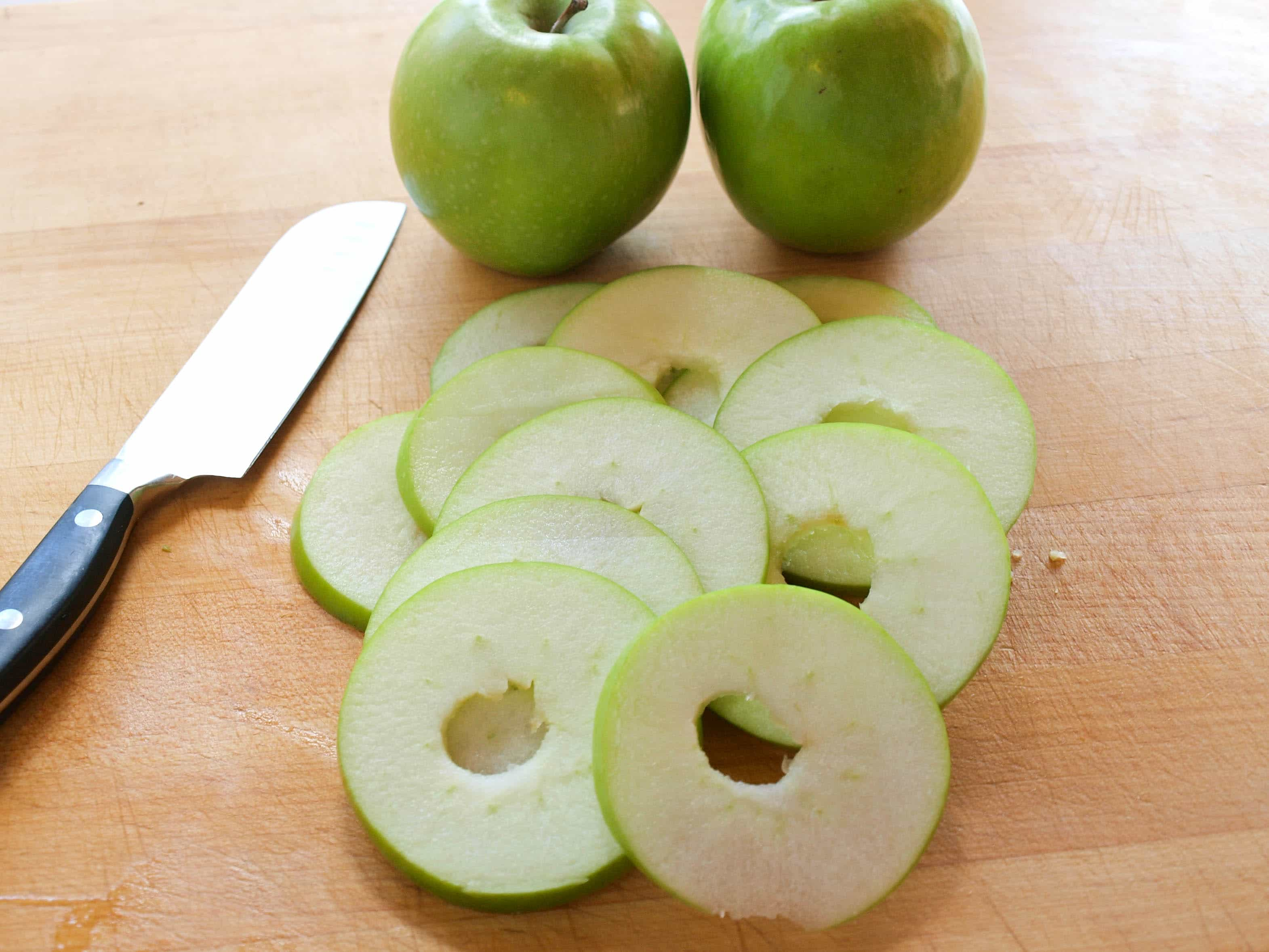 Slicing cored apples into rounds.