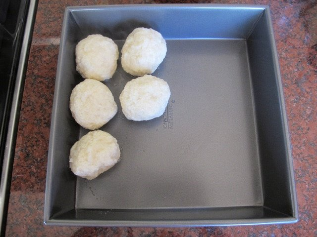 Cooked potato balls in a dish.