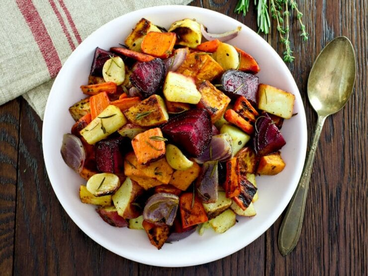 Overhead shot of oven roasted root vegetables with beets, carrots, potatoes, and parsnip. Spoon and fresh herbs on the side, cloth napkin above.