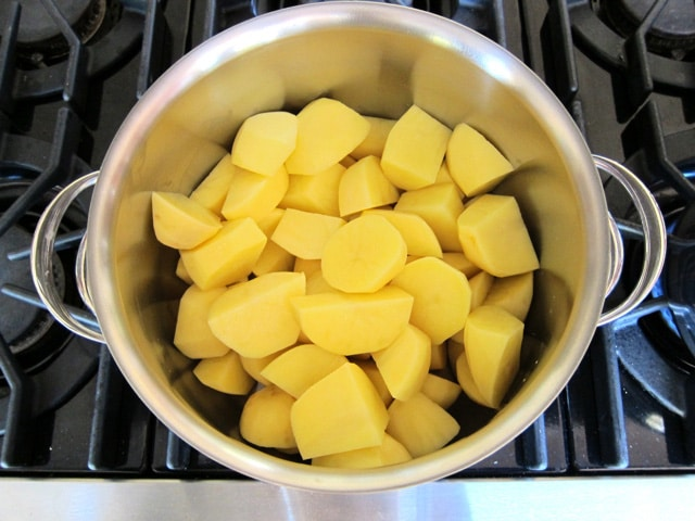 Gold potatoes in chunks in a stockpot.