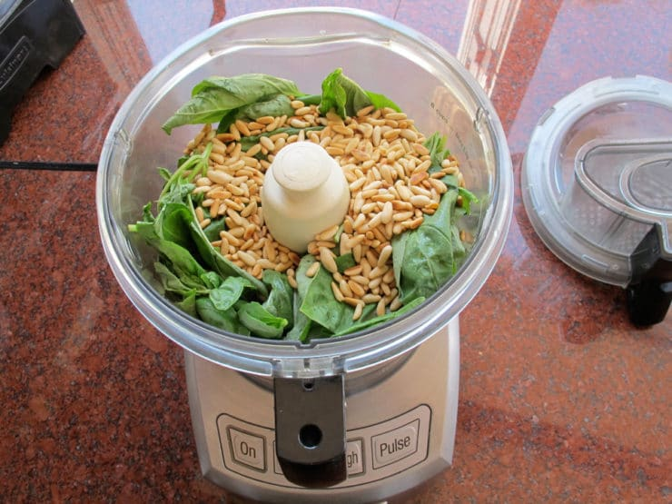 Basil and pine nuts in a food processor.
