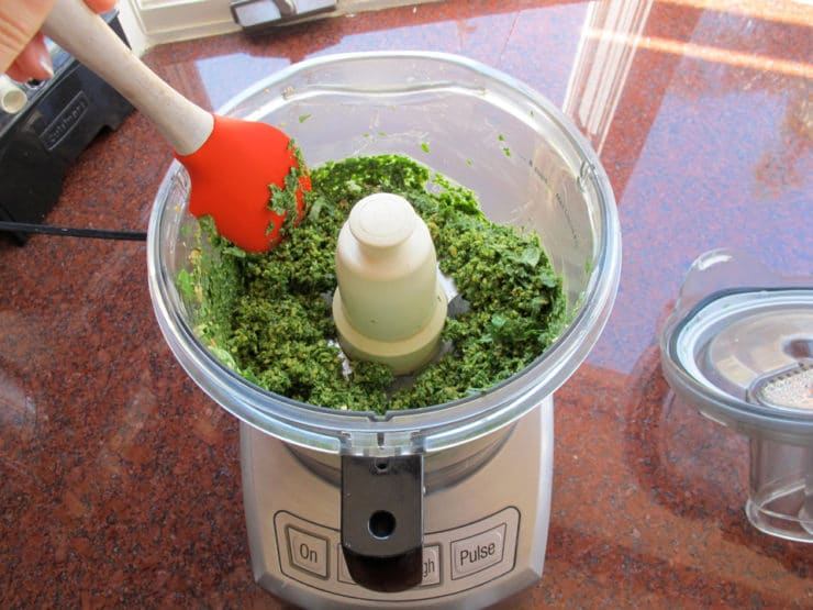 Scraping the sides of the food processor.