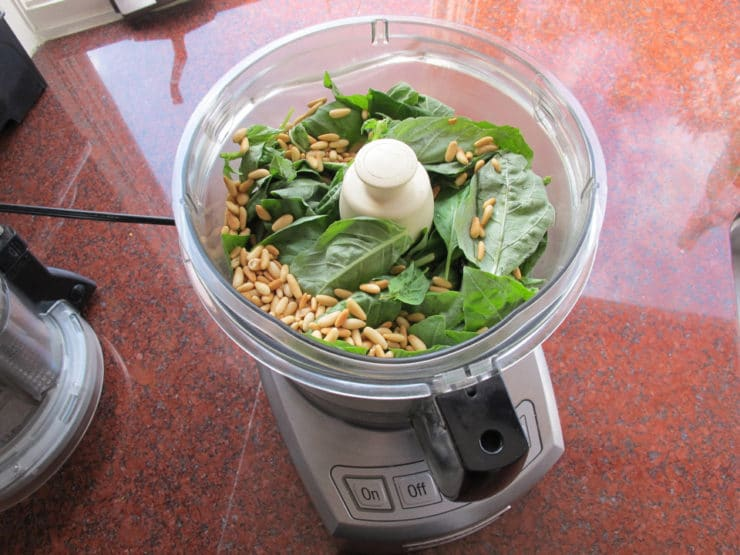 Pine nuts and basil in a food processor.
