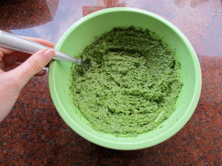 Stirring olive oil into pesto in a bowl.