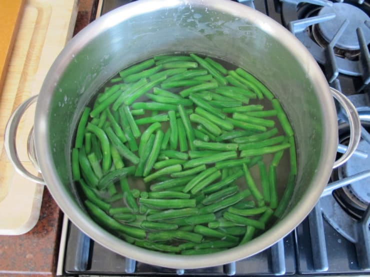 Boiling green beans in a saucepan.