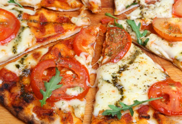 Thin crust pizza margherita with tomatoes, mozzarella, pesto, and ...
