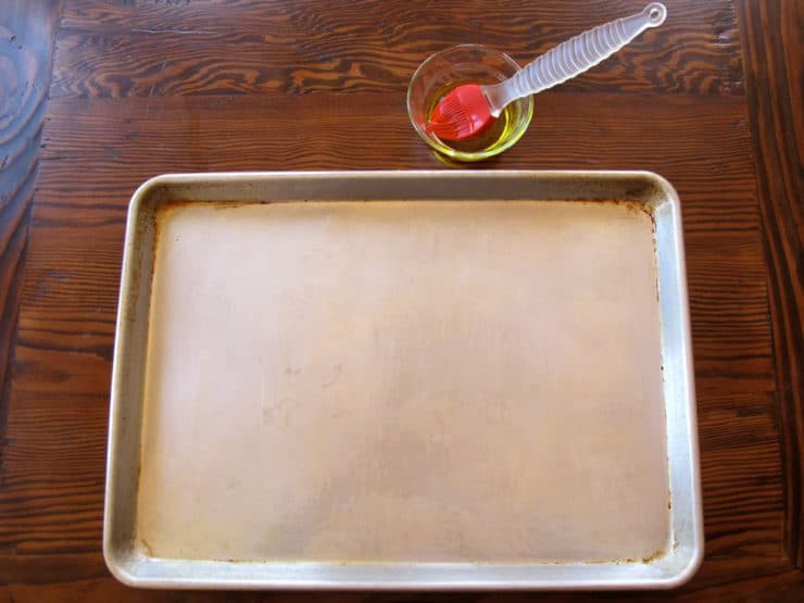 Brushing a baking sheet with olive oil.