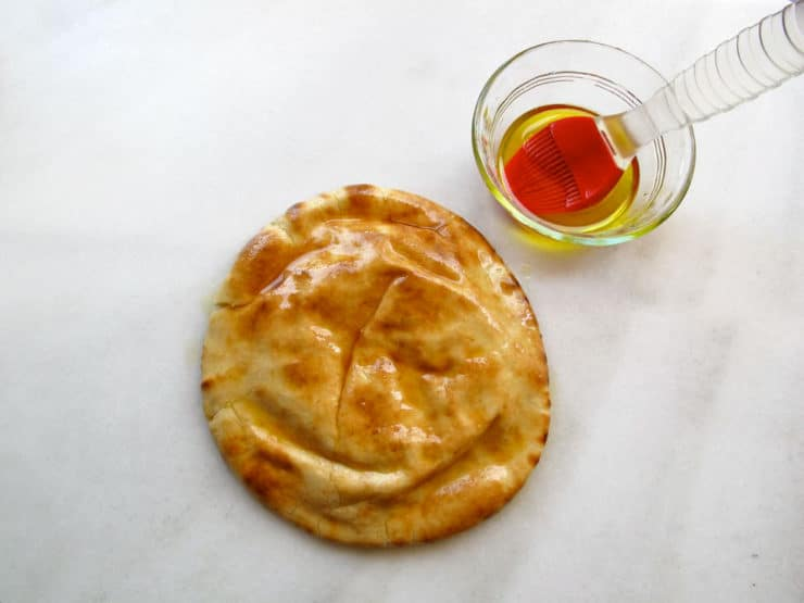 Brushing pita rounds with olive oil.