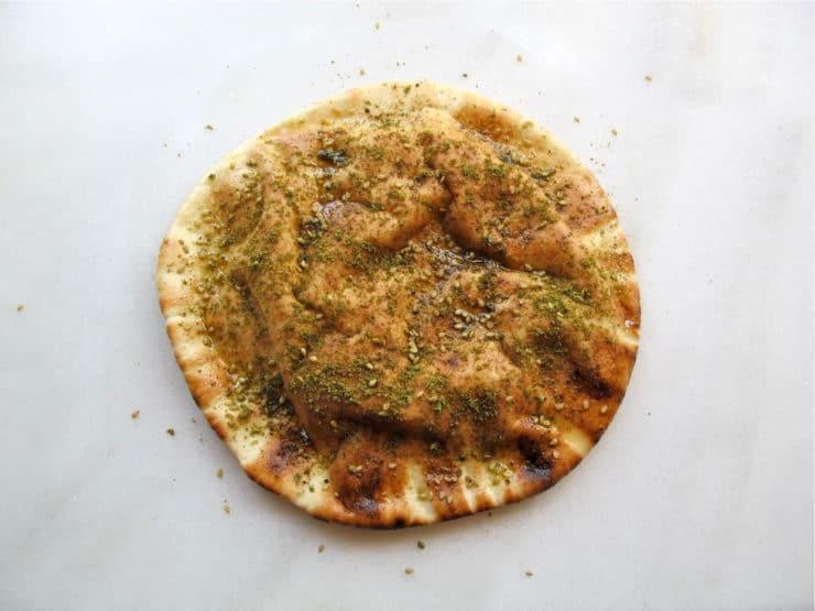 Sprinkling seasoning over oiled pita rounds.