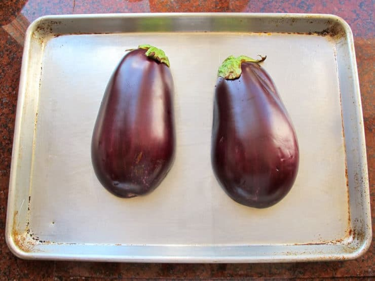 Two fresh eggplant halves on baking sheet.