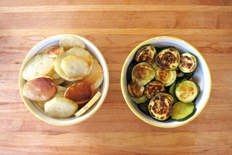 Roasted potatoes and zucchini in separate bowls.