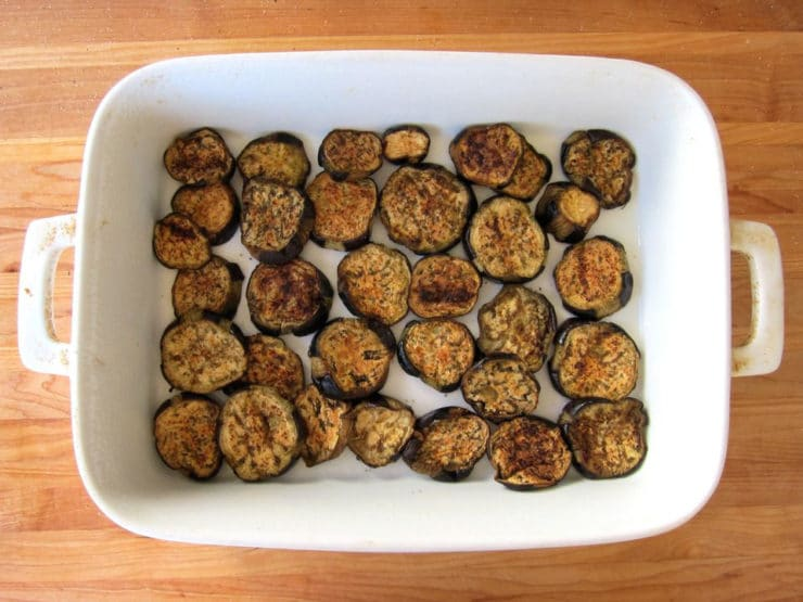 Roasted eggplant layered in a baking dish.