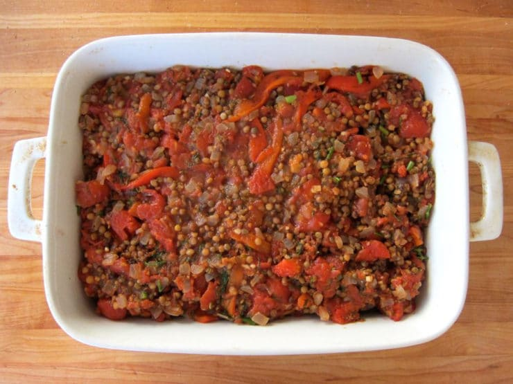 Lentil and vegetable mixture layered in a baking dish.