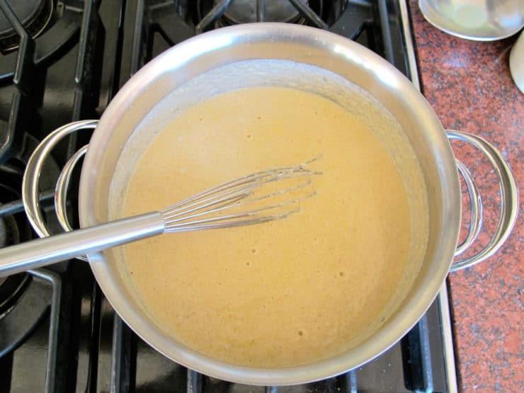 Whisking parmesan cheese into bechamel sauce.