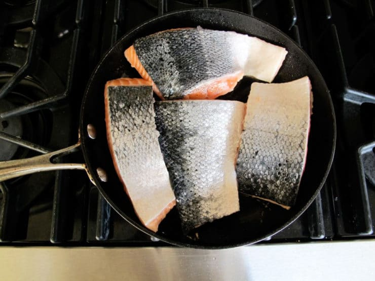 Salmon fillets flesh side down in a skillet.