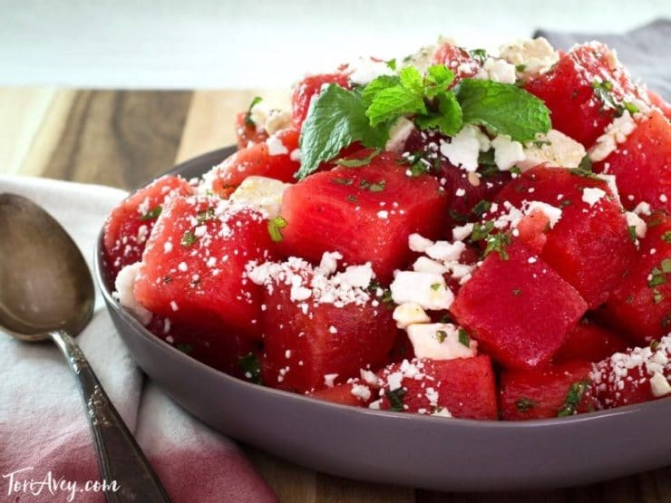 Close up of watermelon feta salad with mint, spoon and napkin beside it.