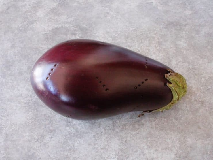 Fresh eggplant pierced with fork on concrete background.