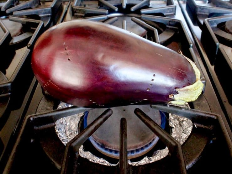 Pierced eggplant on top of foil lined range burner.