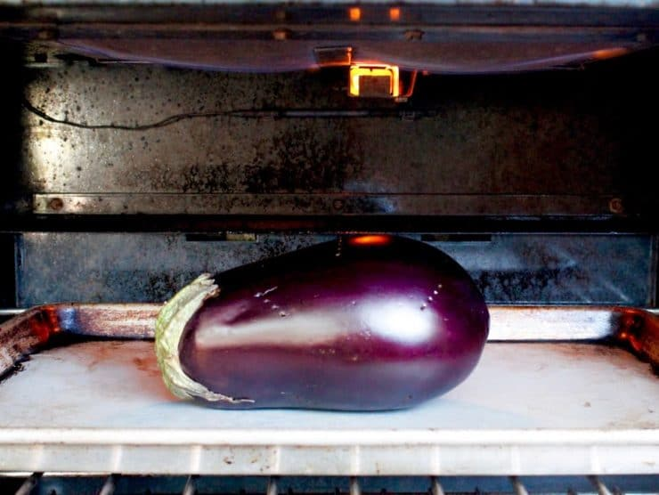 Whole eggplant on baking sheet under broiler.