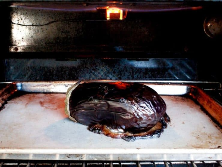 Roasted collapsing eggplant under oven broiler on baking sheet, skin charred.