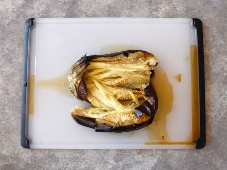 Charred and roasted eggplant sliced open on cutting board.