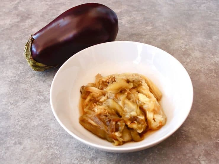 Roasted eggplant pulp in bowl with whole eggplant in background on grey background.
