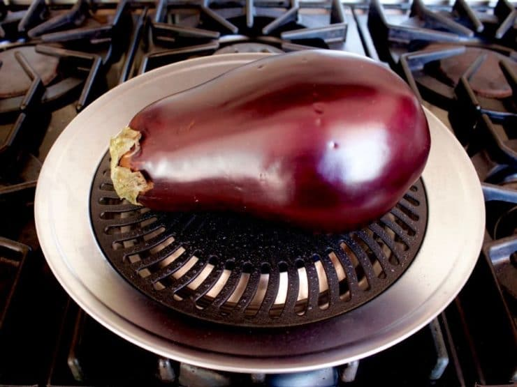 Pierced eggplant on top of grill pan on stovetop.