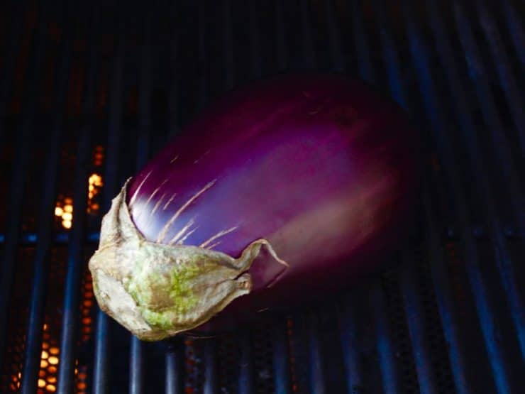 Whole fresh eggplant on grill.