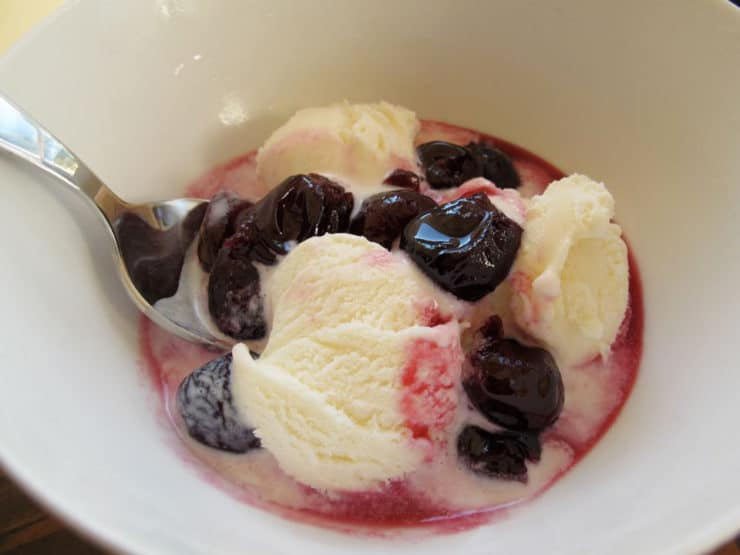 Preserved cherries in a bowl of vanilla ice cream.