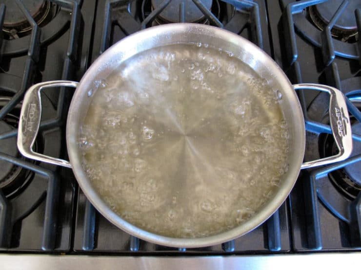 Sugar in boiling water in a saucepan.