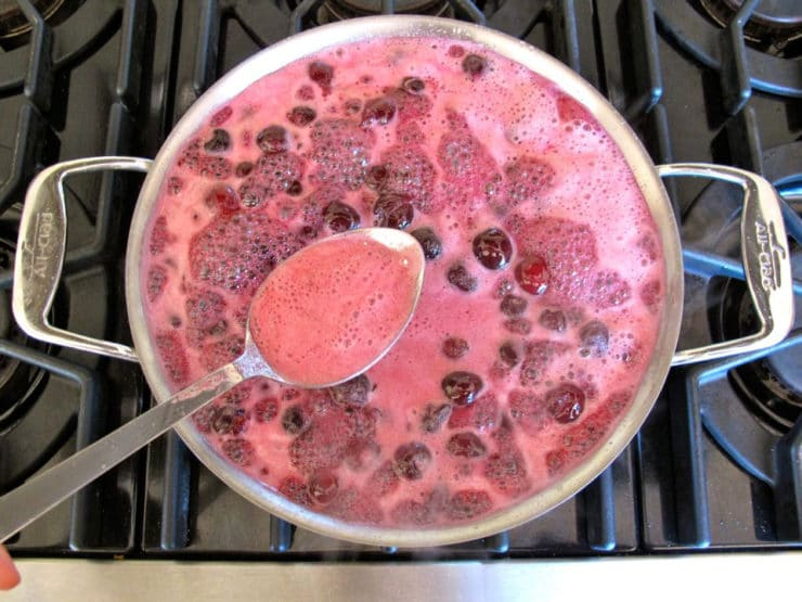 Skimming foam from boiling cherries.