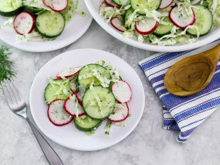 Horizontal shot of two plates of crunchy pickled salad, off to the right is a large bowl of the same salad. A wooden spoon sits on top of a blue and white striped napkin just beneath the bowl.
