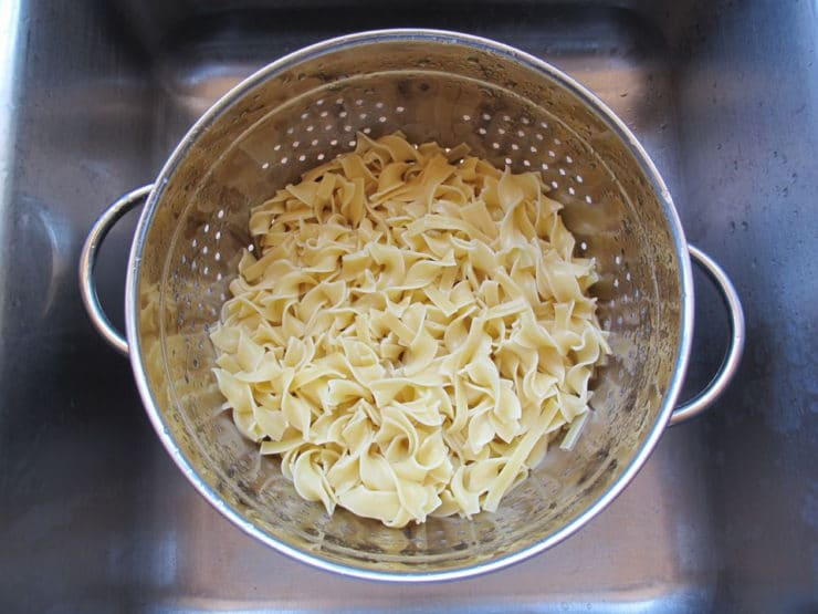 Cooked noodles draining in a colander.