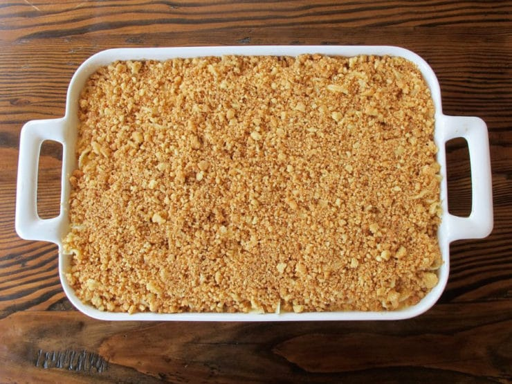 Cookie crumbs over top of noodles in baking dish.