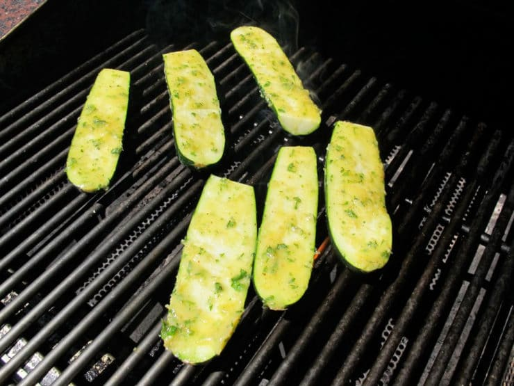 Zucchini halves on a grill, flesh side up.