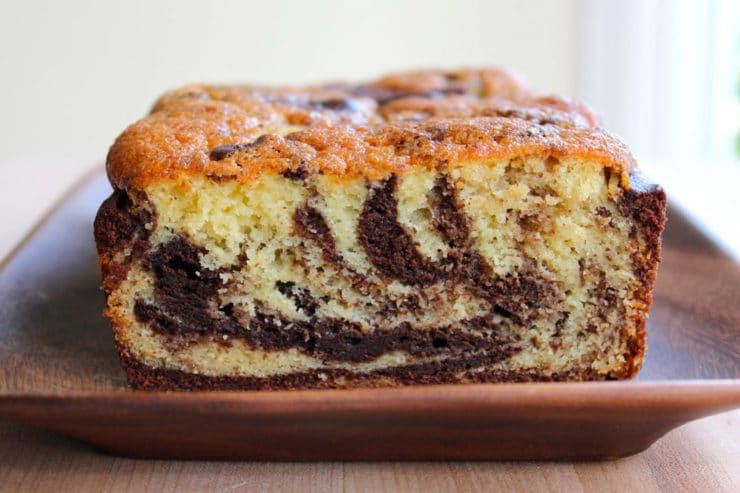 Baked marble cake sliced on wooden tray.