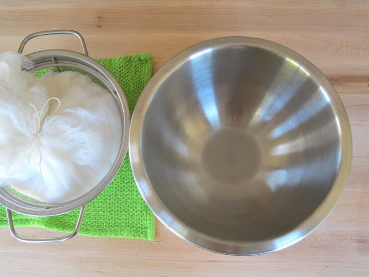 Stainless steel mixing bowl, cheesecloth yogurt bundle in mesh strainer.
