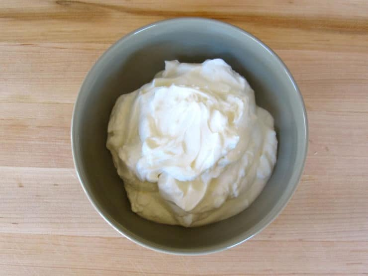 Thickened strained yogurt in bowl on cutting board.