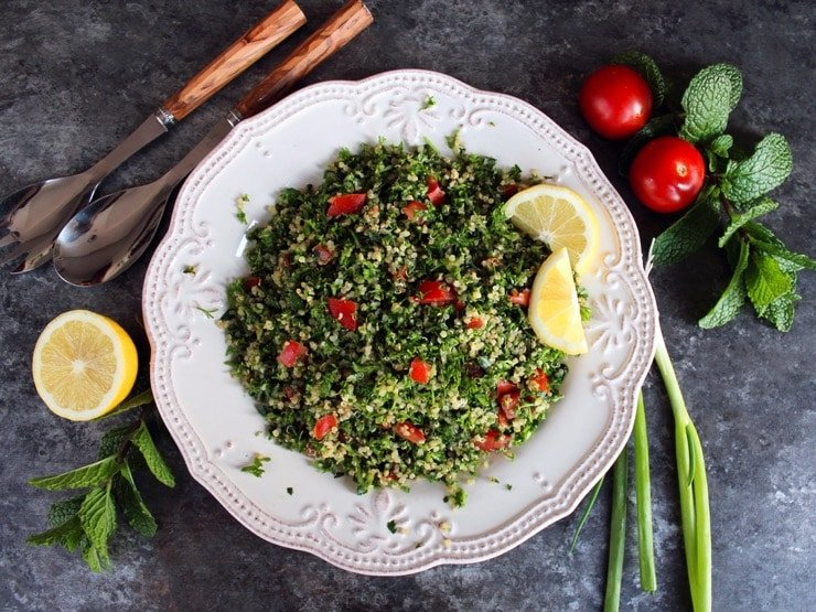Overhead shot of quinoa tabbouleh salad in a white dish with lemon slices, half lemon, mint sprigs, green onions and small tomatoes. Salad fork and spoon on the upper left of the dish.