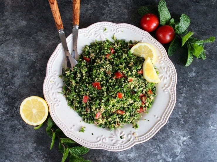 Overhead shot of quinoa tabbouleh salad in a white dish with lemon slices, half lemon, mint sprigs, green onions and small tomatoes. Salad serving utensils with wooden handles rest in the salad.