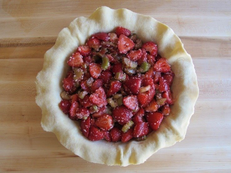 Pie crust in pie dish filled with strawberry rhubarb filling.