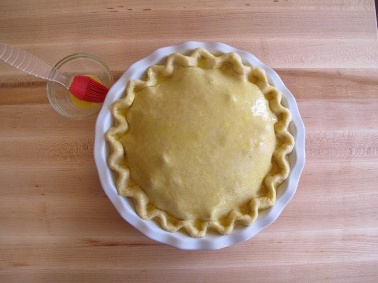 Brushing pie crust with egg wash using silicone brush on wooden background.