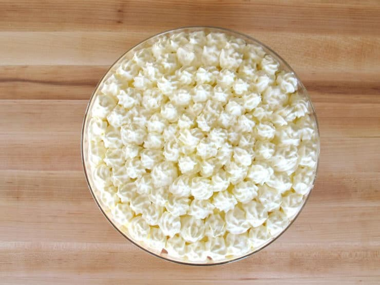 Piping whipped cream stars on top of trifle.