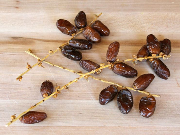 Three small branches of juicy ripe dates on a wooden cutting board.