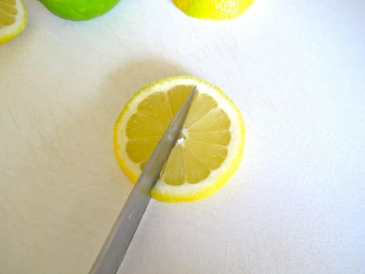 Slice lemon round nearly in half.