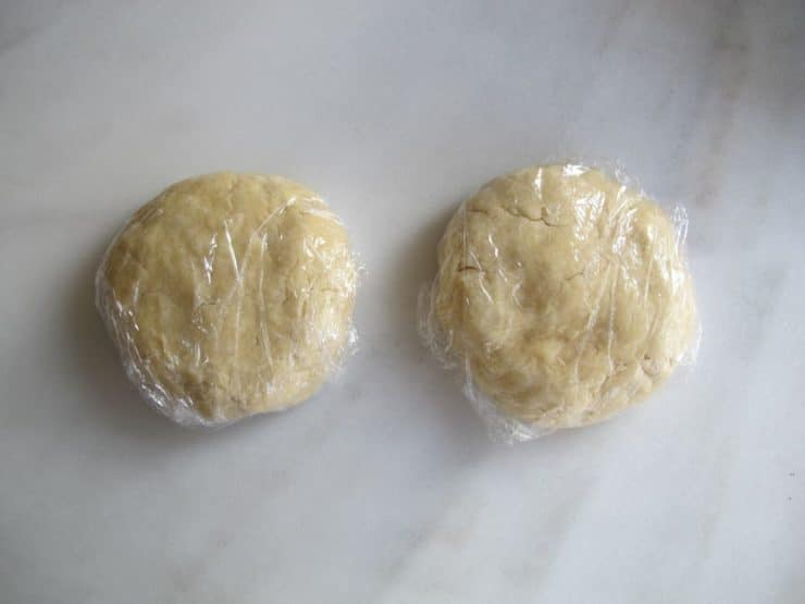Two disks of pie crust dough wrapped in plastic on marble board.