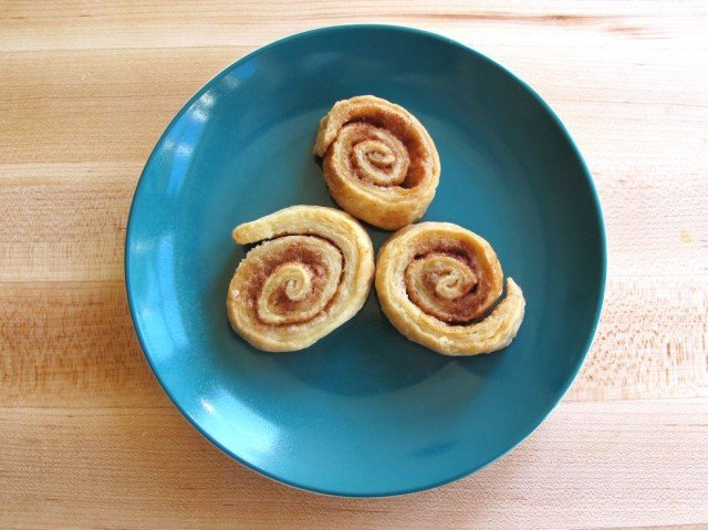 Three pie crust pinwheels on blue plate on wooden cutting board.