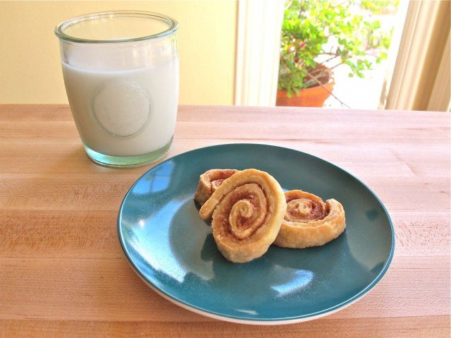 Three pie crust pinwheel treats on a blue plate on wooden cutting board with glass of milk.